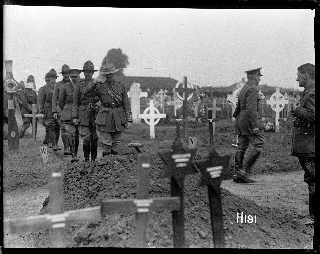 Officers saluting the grave of a fallen comrade