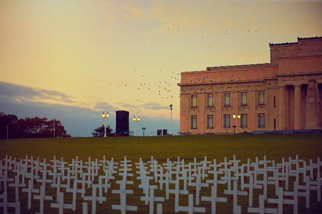 Auckland Museum at dawn with field of white crosses.