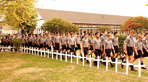 Boys walk between the crosses of Fallen Old Boys