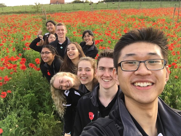 Students in a field of poppies